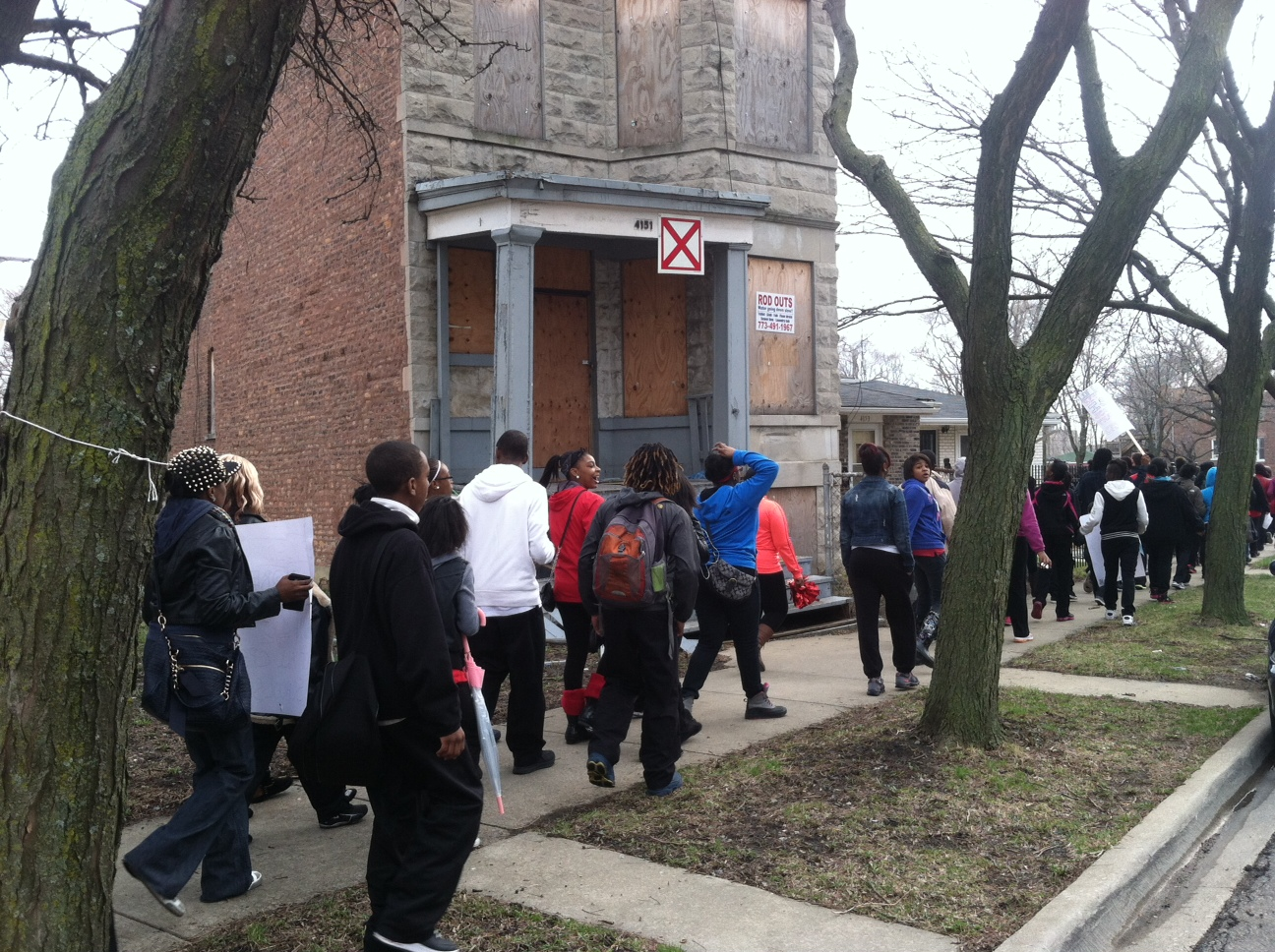 "Parents and students walk past one of the many abandoned buildings on the proposed CPS route to the ""welcoming"" school."